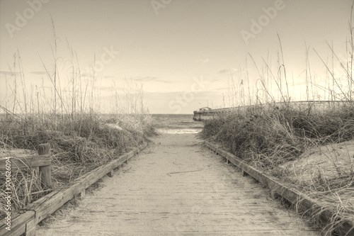Atlantic Ocean Background. Boardwalk through dune grass to the Atlantic Ocean with a pier in the background. Myrtle Beach, South Carolina.