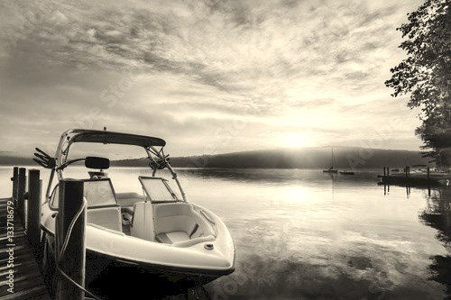 Sun and mist on boat dock at sunrise on a summer day. Merrymeeting Lake, New Hampshire