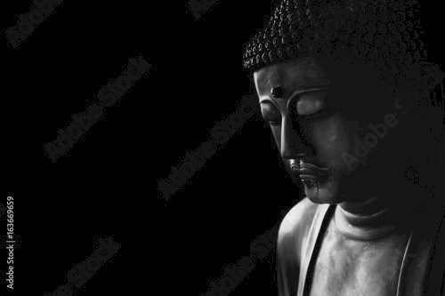 closeup face of zen stone art buddha in dark for background asian way tranquil of meditation and religious.