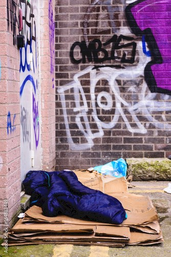A sleeping bag and cardboard boxes on the ground in an alleyway behind an office block, used by a homeless person to sleep.