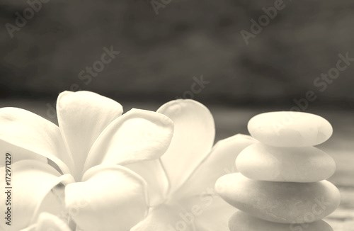 Pile of black zen stones and Frangipani flower on rustic wood background