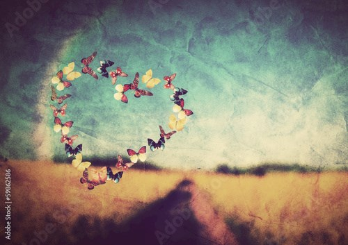 Heart shape made of butterflies on vintage field background