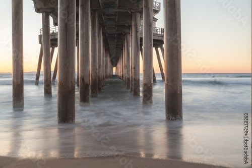 Under the Huntington Beach, California pier at sunset in the fall