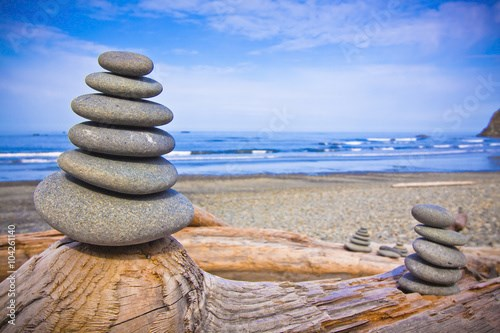 rocks balanced on the driftwood by seashore