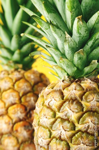 Ripe pineapples on a yellow wooden background