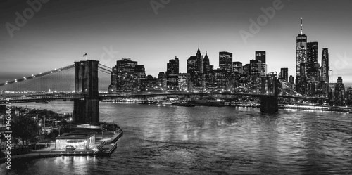 Black & White elevated view of the Brooklyn Bridge and Lower Manhattan skyscrapers at dusk. Skyline of the Financial District with East River. New York City