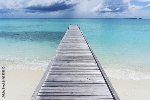 Wooden pier over tropical clear blue sea