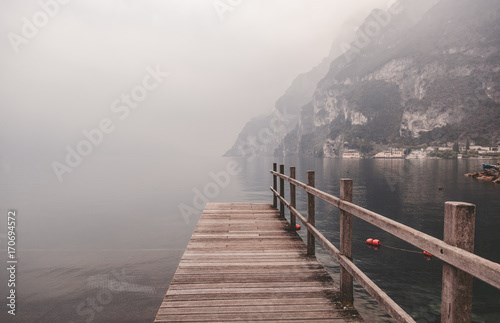 Wooden pier on the lake against the backdrop of the mountains, Garda, Italy