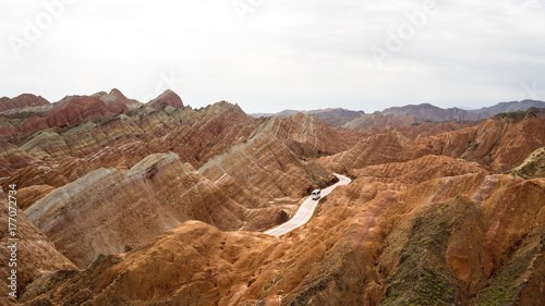 The bus is riding in the middle of rainbow mountains of china (Zhangye Danxia landform Geological park), Zhangye, Gansu province, which was named a UNESCO world heritage site in 2009.